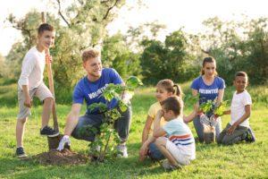Kids planting trees with volunteers in park
